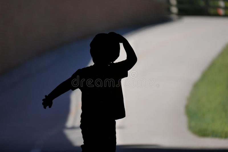 Силуэт молодого хода мальчика стоковые изображения