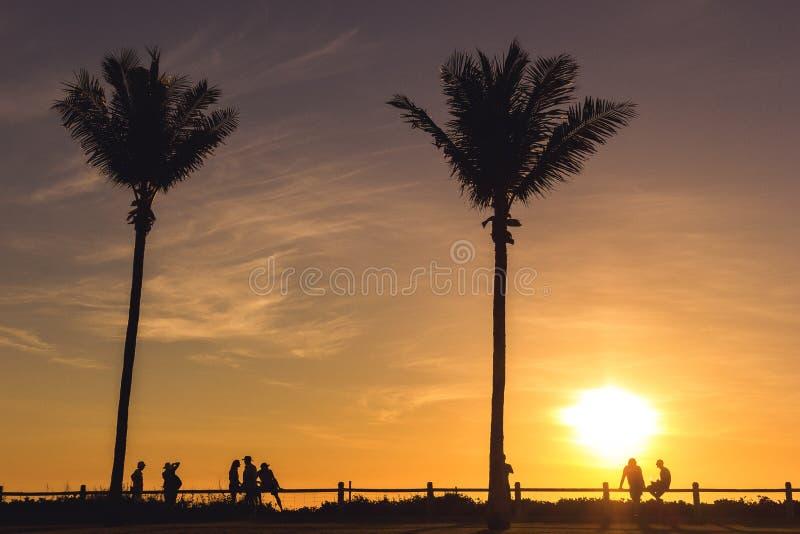 силуэт туристов, locals и друзей enyoing заход солнца с напитком на пляже в Broome, западной Австралии стоковое изображение rf
