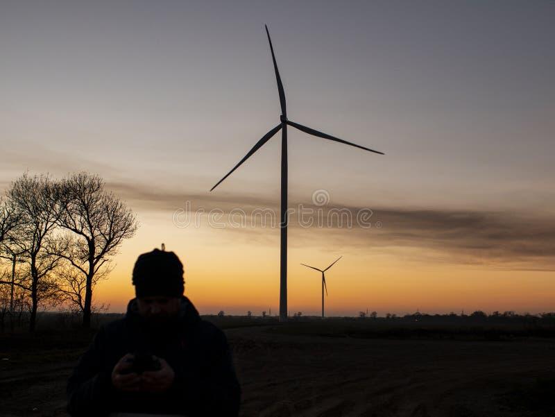 Силуэт человека на заходе солнца делая фото из ветротурбин Электрические станции энергии ветра на заходе солнца стоковое изображение rf