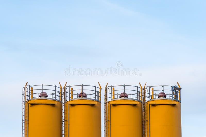 4 силосохранилища перед голубым небом стоковое фото