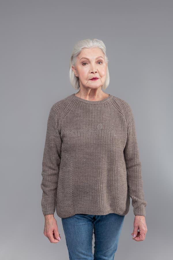Симпатичная аккуратная старшая женщина нося серый связанный свитер стоковое фото