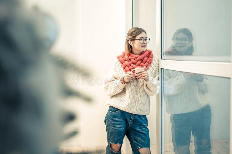 Симпатичная стильная дама оставаясь с чашкой чаю и нося связанным обмундированием стоковое изображение