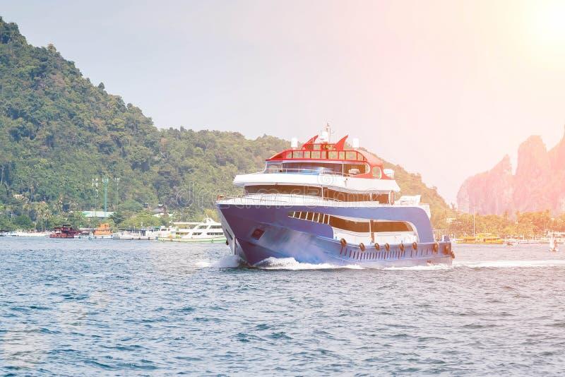Синь с белой и красной шлюпкой скорости удовольствия акцентов Плавание на море против тропического острова Вид спереди стоковые изображения
