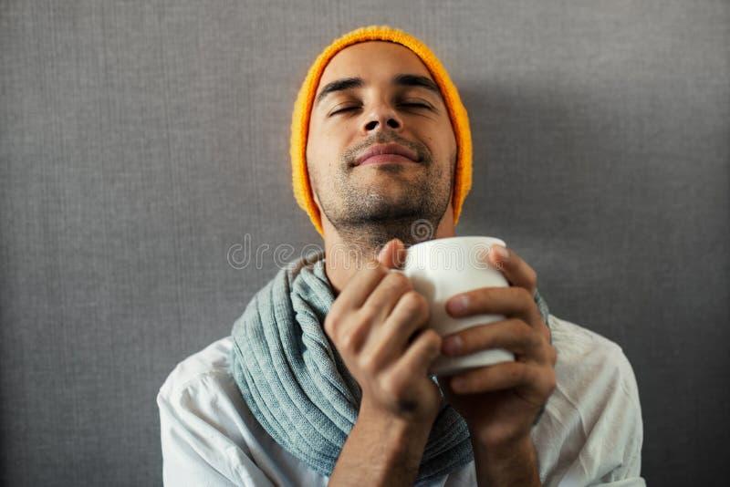 Сидя молодой красивый человек с кружкой кофе, чая, воды Мечтать и усмехаться с закрытыми глазами на серой предпосылке стоковая фотография rf