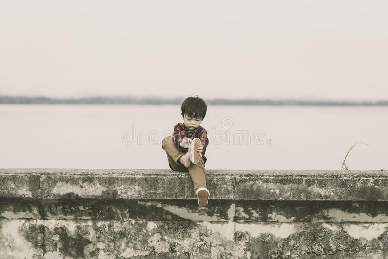 Сиротливые дети принимают ботинки и он сидит на том основании стоковая фотография