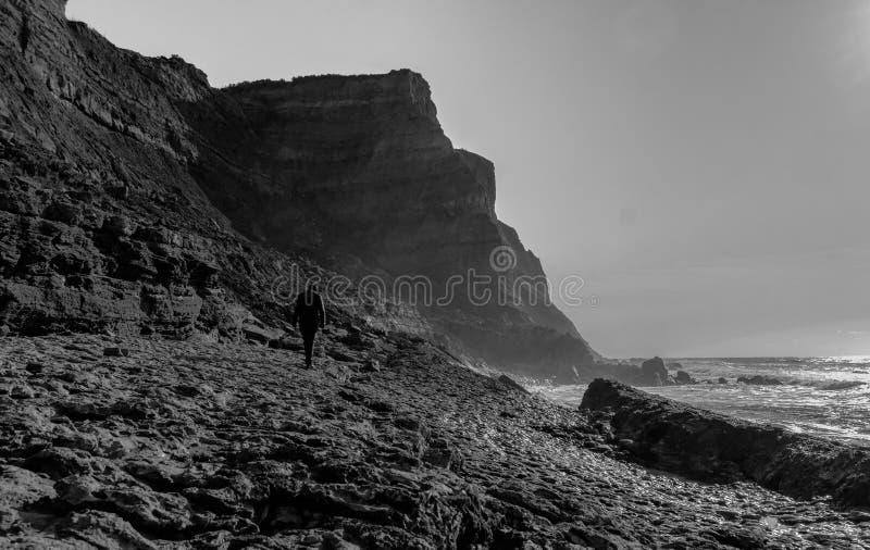 Скала и силуэт человека морем на пляже Ericeira Порту Barril, белого и черно-, Mafra - Португалии стоковые изображения