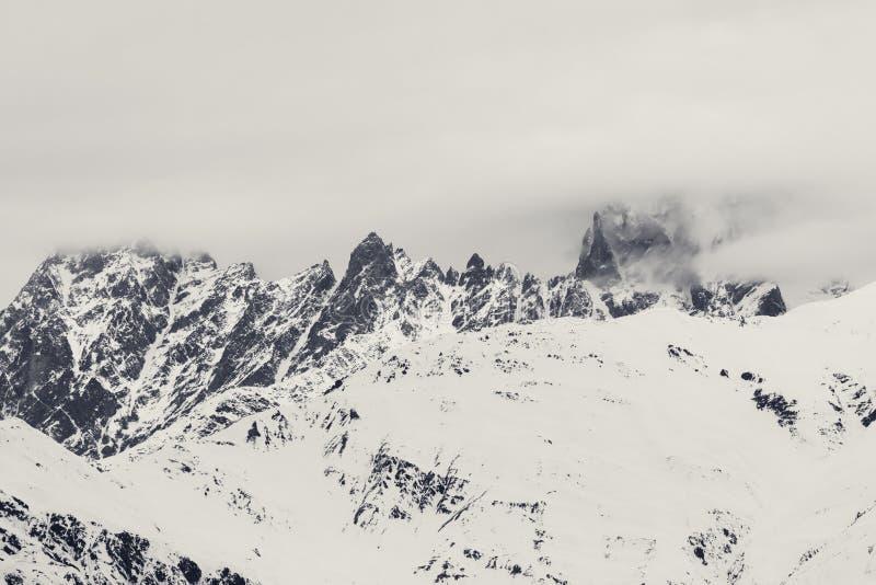 Скалистые горы в небе снега и overcast сером стоковые изображения