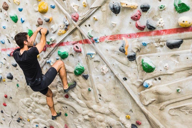 Скалолазание человека практикуя на искусственной стене внутри помещения Активный образ жизни и bouldering концепция стоковое фото rf
