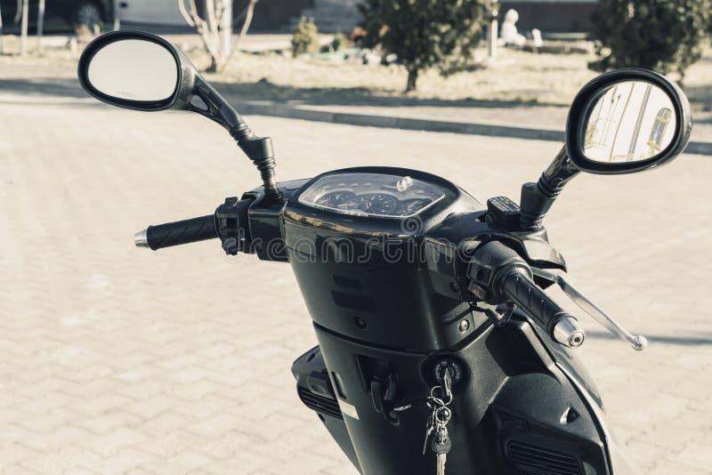 Скутер стоит на улице города Владелец забыл ключи стоковое фото rf