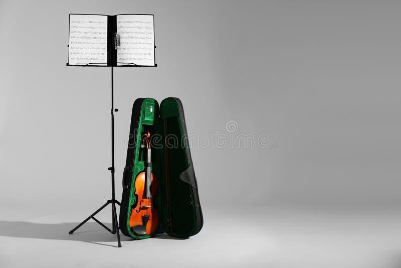 Скрипка в случае если и стойка примечания с листами музыки на сером цвете Космос для текста стоковая фотография rf