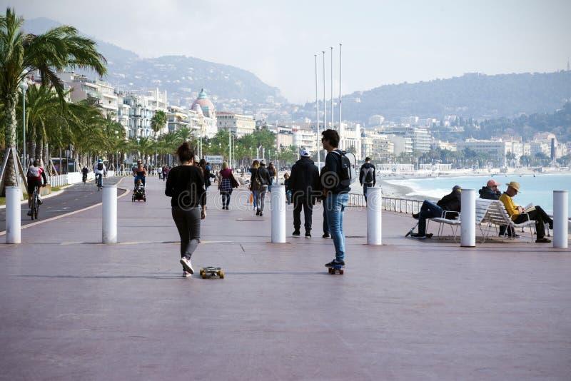 Славный, Франция, март 2019 2 молодые люди: мальчик и езда девушки скейтборд вдоль прогулки ` Azur Коута d стоковые фотографии rf