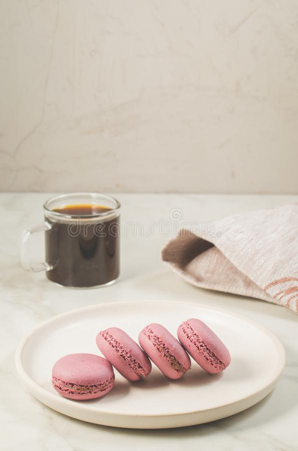 Сладкие macaroons или macaron на белых шаре и кофе в стекле на белой таблице пудинг франчуза fondant шоколада стоковое изображение rf