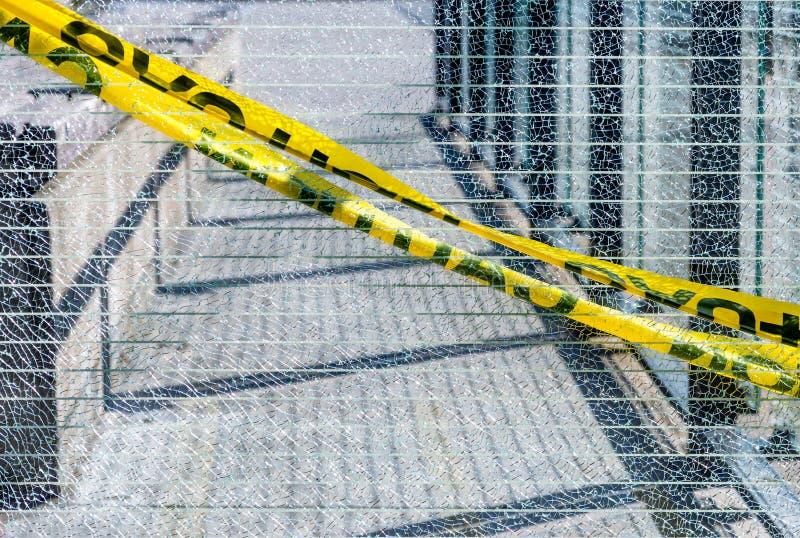 Сломленная панель ячеистой сети стеклянная с желтой лентой предосторежения протянула поперек в раскосной моде стоковые фотографии rf