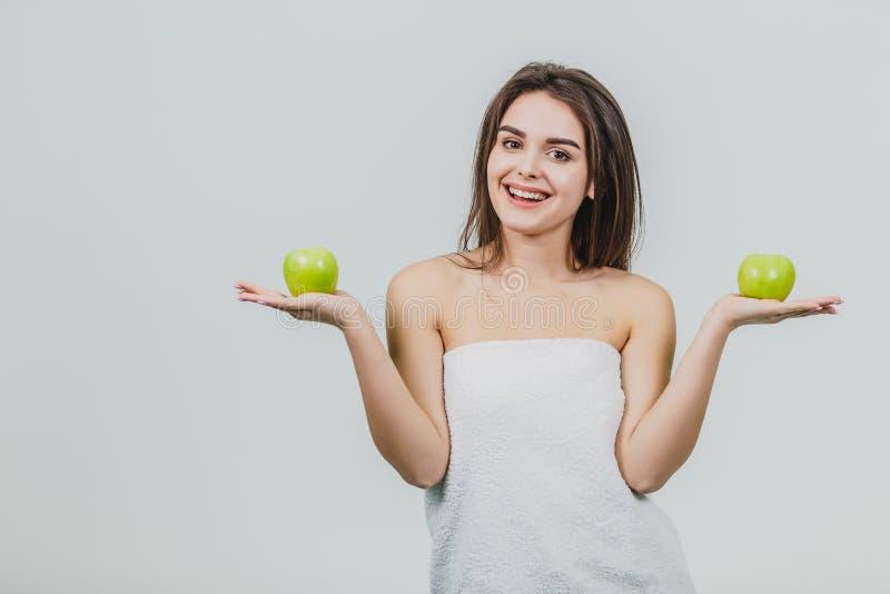 Смешная смеясь женщина держа 2 зеленых яблока в ее глазах Белая предпосылка здоровой концепции еды Диета стоковое фото