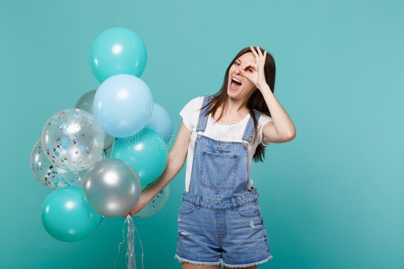 Смешная рука удерживания молодой женщины около глаза, имитирующ стекла или бинокли, празднуя с красочными воздушными шарами стоковое фото