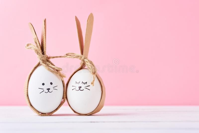 Смешные домодельные яйца со сторонами на розовой предпосылке Пасха или счастливая концепция пар стоковые изображения