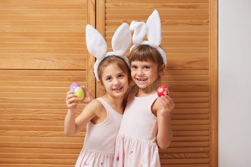 2 смешных очаровательных маленьких сестры в платьях с белыми ушами кролика на их головах держат покрашенные яйца в их руках стоковая фотография
