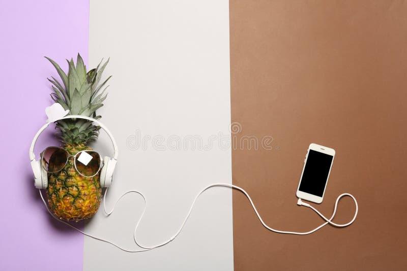 Смешной ананас с наушниками, смартфоном и солнечными очками на предпосылке цвета, плоском положении стоковые изображения rf
