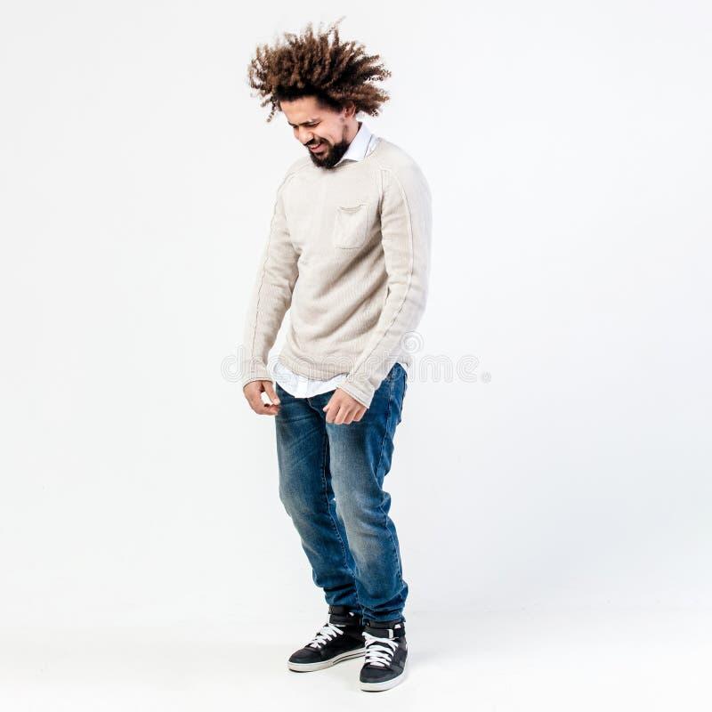 Смешной коричнев-с волосами курчавый парень с бородой одетой в бежевом прыгуне над белой рубашкой и представлениях джинсов в студ стоковые фотографии rf
