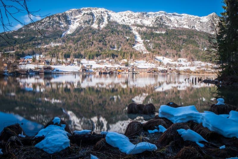 Снег покрыл берег озера на озере Grundlsee с горами Klammkogel, Hundskogel стоковое изображение
