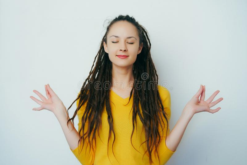 Спокойная здоровая красивая девушка с dreadlocks и в желтом ярком свитере размышляя для сброса стресса с глазами закрыла, усмехаю стоковое изображение