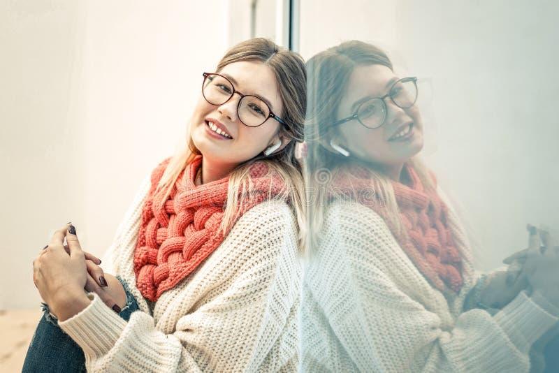Спокойная симпатичная дама полагаясь на стекле окна стоковые фото