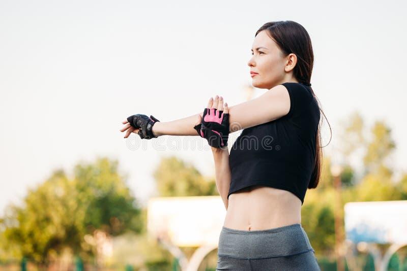 Спортзал молодой женщины в парке Пригодность в природе Тренировка утра с красивым, женщина спорта Девушка делая разминку в парке  стоковое изображение rf