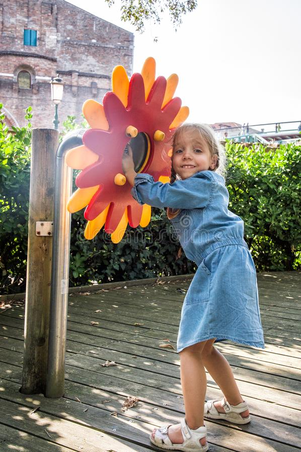Спортивная площадка в Венеции Очаровывая девушка в голубом платье смеется близко от телефона цветка Концепция: консервные банки т стоковая фотография