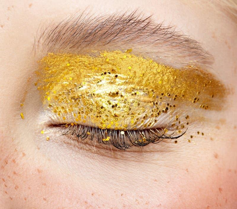 Съемка макроса крупного плана закрытого человеческого женского глаза с желтым закоптелым макияжем красоты глаз стоковые изображения