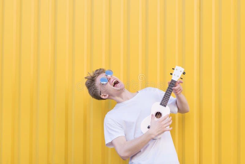 Сумасшедший молодой человек играет гавайскую гитару на желтой предпосылке Выразительный музыкант играя гитару Музыкальная принцип стоковое фото