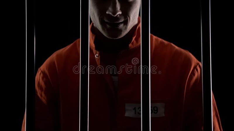 Сумашедшее положение серийного убийцы за барами тюрьмы и ухмыляться, расстройство рассудка стоковое фото rf