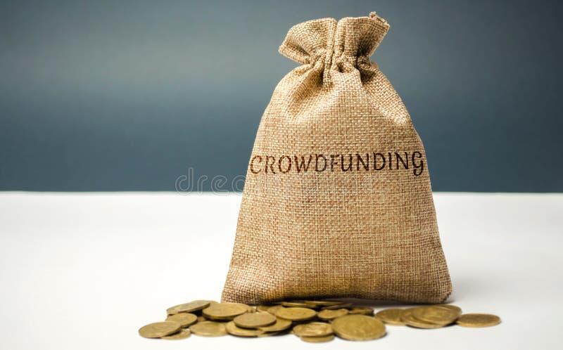Сумка денег с монетками со словом crowdfunding Добровольная организация денег или ресурсов через интернет Получатели поддержки стоковые изображения rf