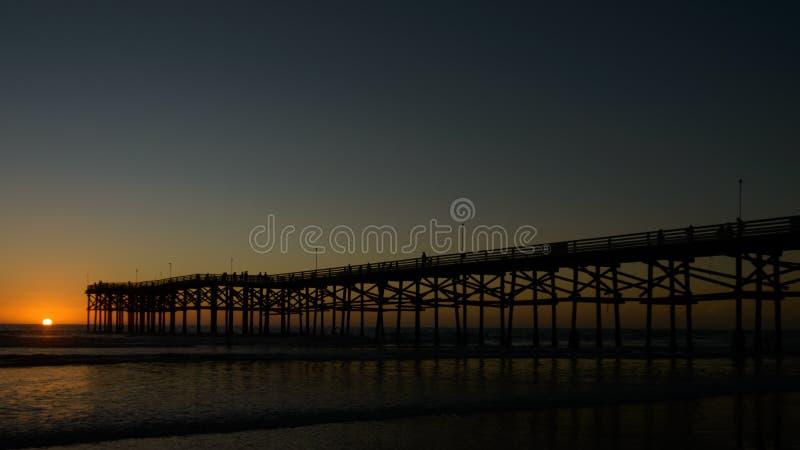 Сумрак падает на пристань на Тихом океан пляже стоковые фотографии rf
