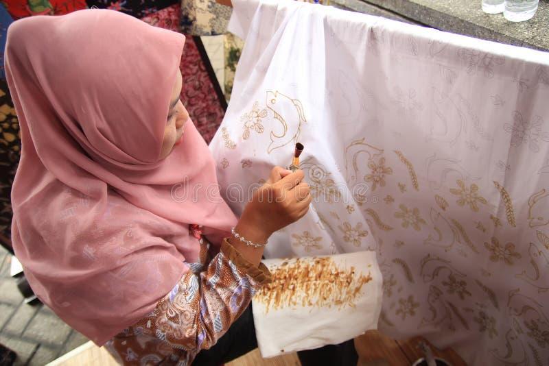 Сурабая Индонезия 20-ое августа 2015 Женщина делает мотив батика используя наклонять стоковое фото