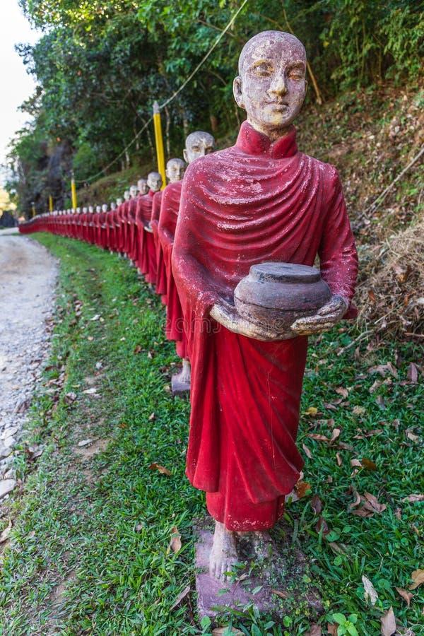 Статуи буддийских монахов каменные гребут на пещере Thaung Ka Kaw, Hpa-an, Мьянме стоковые изображения rf