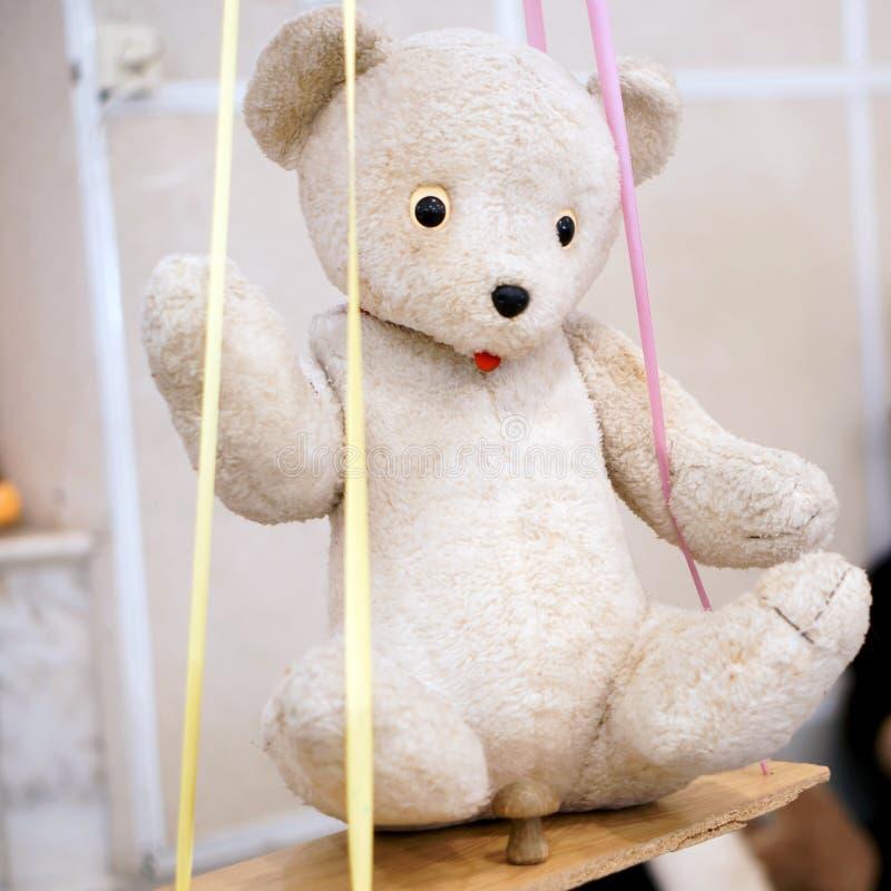 Старая игрушка - винтажный белый медведь плюша сидя на качании стоковые фотографии rf