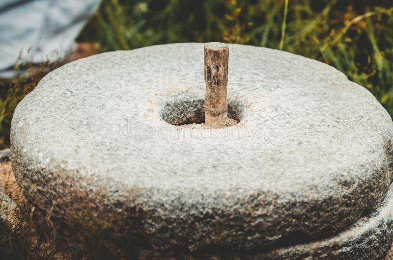 Старая каменная мельница руки с зерном Пшеница средневекового управляемого рук жернова меля Старая мельница руки камня quern с стоковые фото