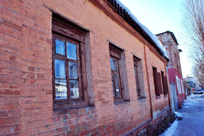 Старая красная стена кирпичного здания с окнами близко вверх, улицей зимы маленького города, снегом на крыше и деревом тополя без стоковая фотография