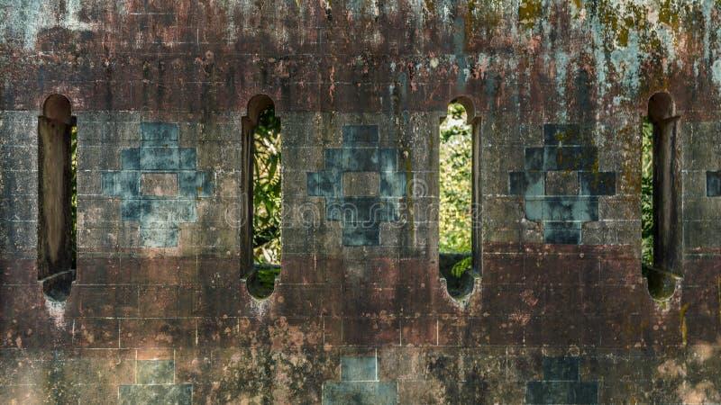 Старая стена с вычисляемыми отверстиями и крыть черепицей черепицей картинами стоковые фото