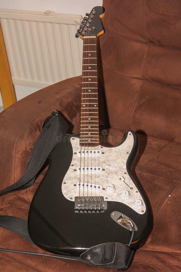 Старая черная белая электрическая гитара на кресле стоковые изображения rf