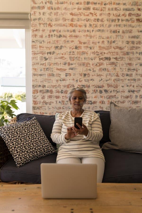 Старшая женщина используя мобильный телефон в живущей комнате стоковое фото