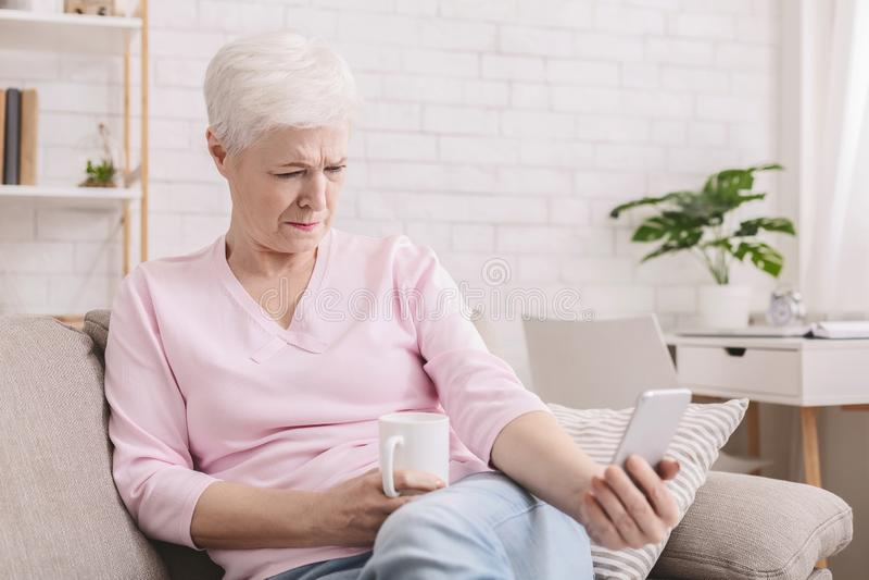 Старшая женщина с проблемами зрения использующ телефон стоковая фотография rf