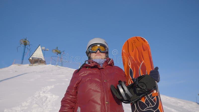Старшая женщина с положением сноуборда на снежном наклоне на курорт зимы в горе стоковое фото rf