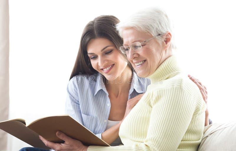 Старшая мать и дочь смотря каталог, ища новый дом стоковая фотография rf