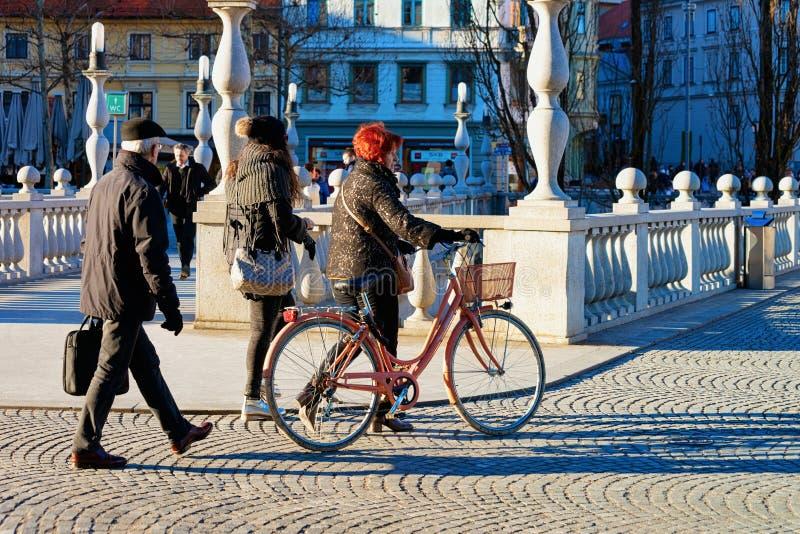 Старшие женщина и велосипед в улице Любляны стоковая фотография