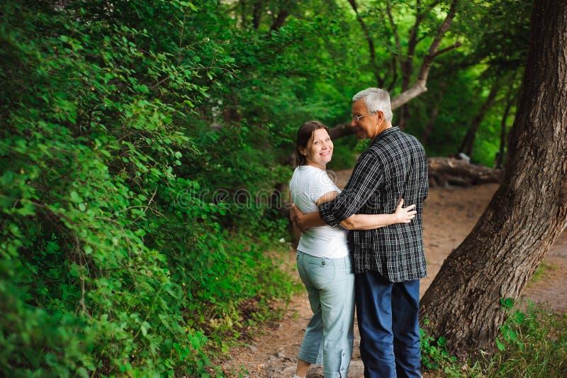 Старшие пары идя совместно в лес, конец-вверх стоковое изображение