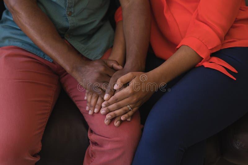 Старшие пары держа руки в живущей комнате стоковое изображение rf