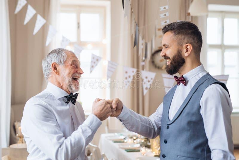 Старший и зрелый человек стоя внутри помещения в наборе комнаты для партии, делая рему кулака стоковые фото