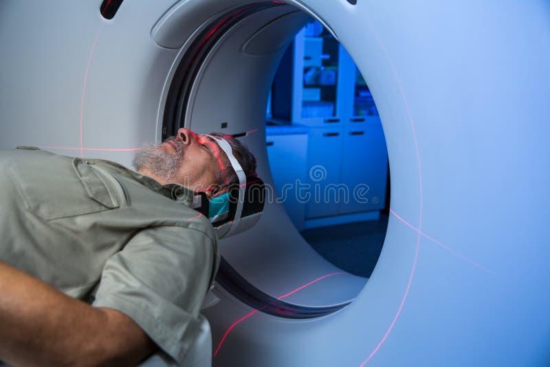 Старший мужской пациент проходя рассмотрение MRI в современной больнице стоковые фотографии rf