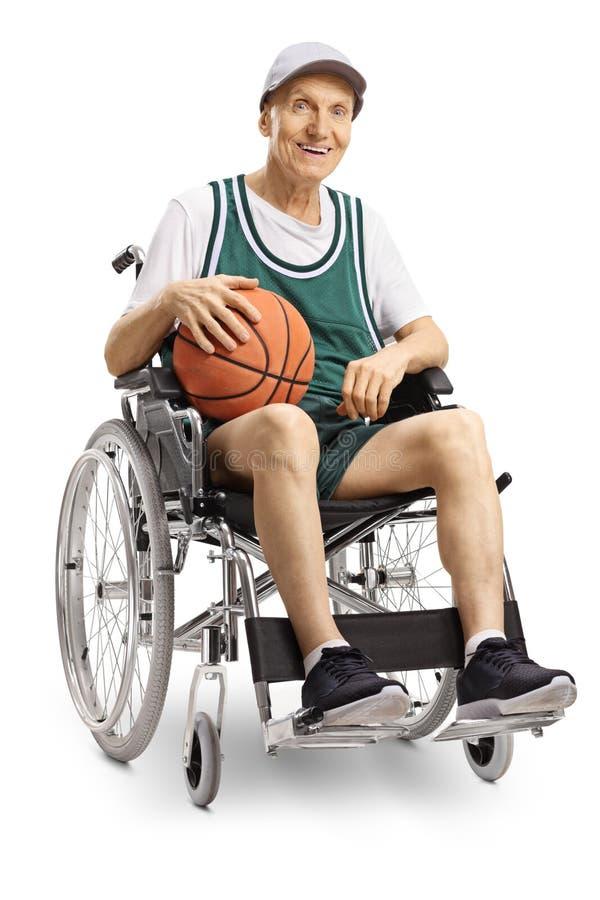 Старший неработающий человек держа баскетбол и сидя в кресло-коляске стоковые фото